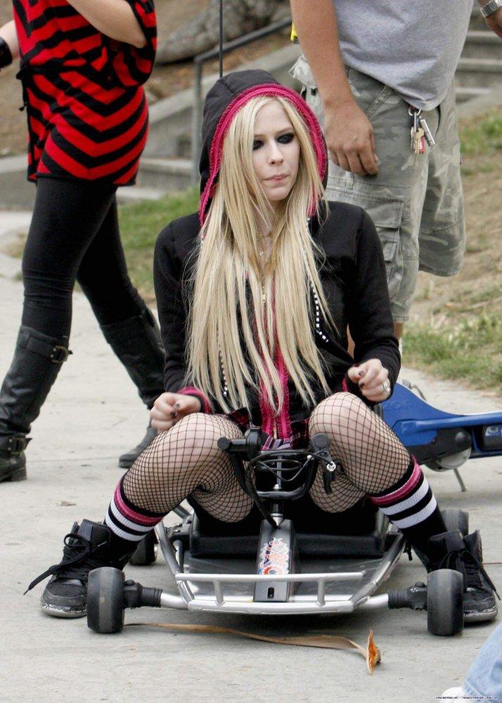 Avril Lavigne squats on a go board
