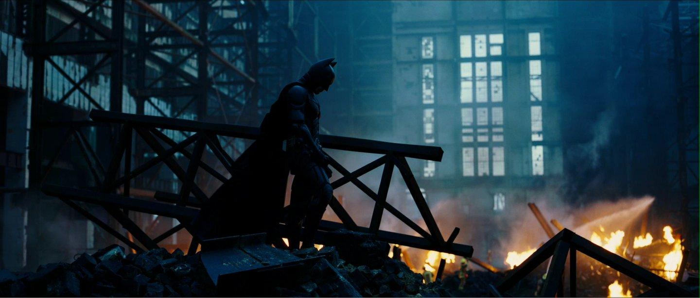 Batman stands on rubble