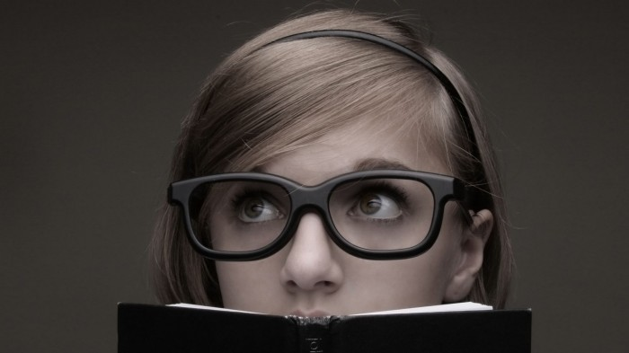 nerdy girl looking over a book
