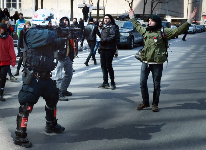 Montreal cop points grenade launcher at protester.jpg